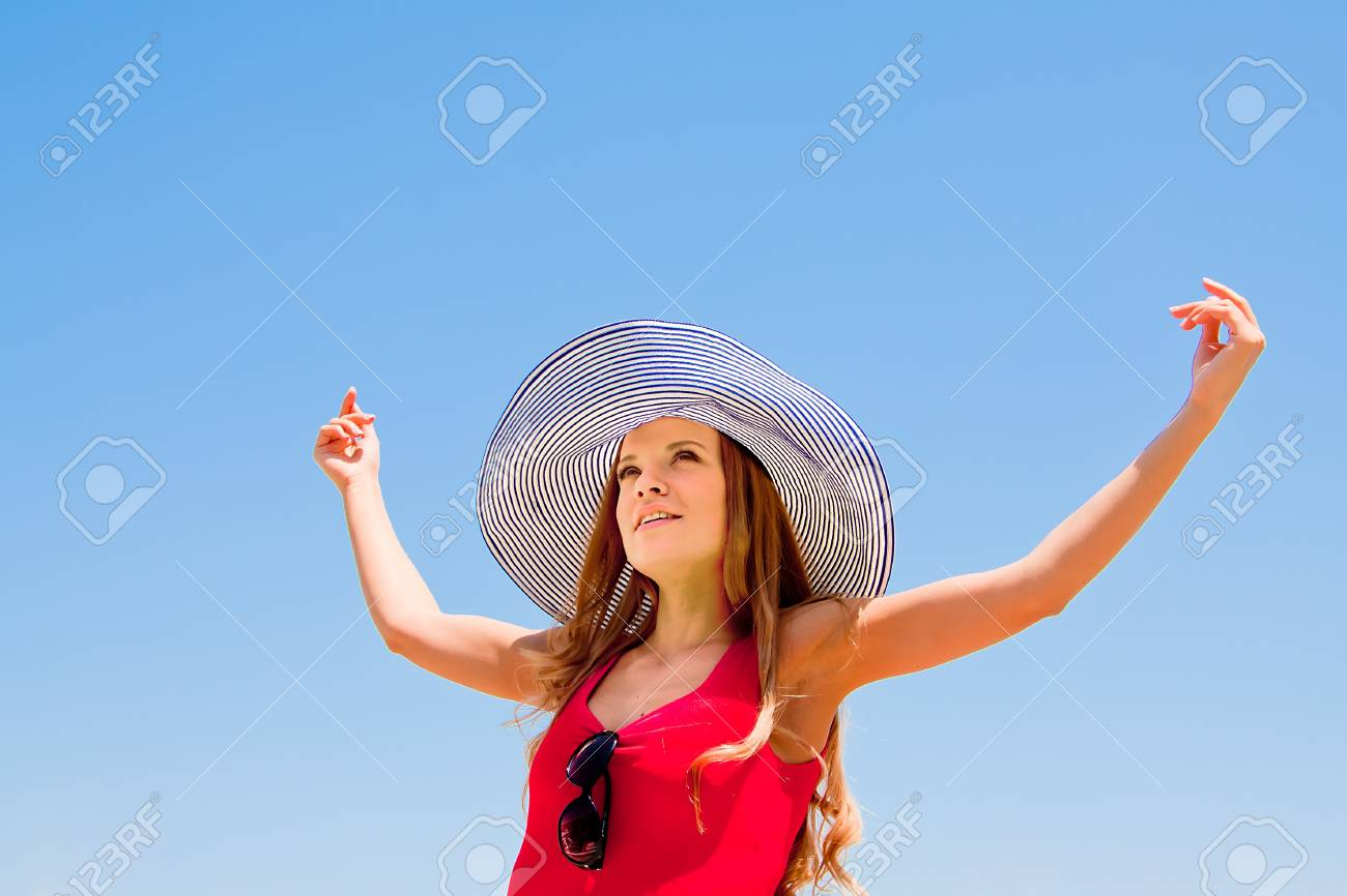 happy young beautiful girl in a beach hat in the sky Stock Photo - 13777326