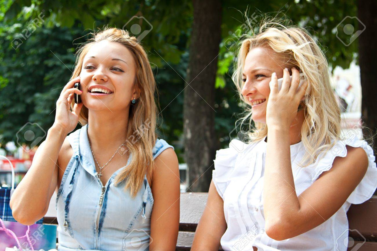 Two beautiful young women talking on the phone while sitting on a park bench Stock Photo - 15384468