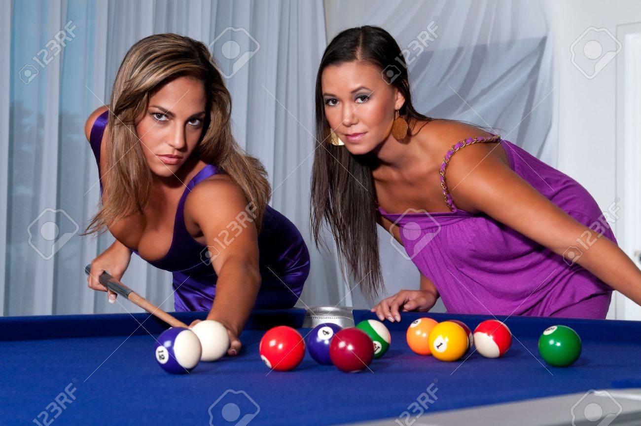 2 young womans playing pool looking at camera very sensual. Stock Photo - 5644959