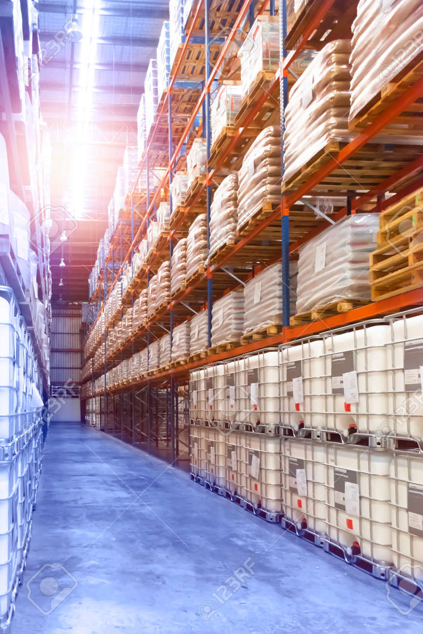 Large distribution warehouse interior, pallets and boxes of cargo stack on row of high shelves. - 149806696
