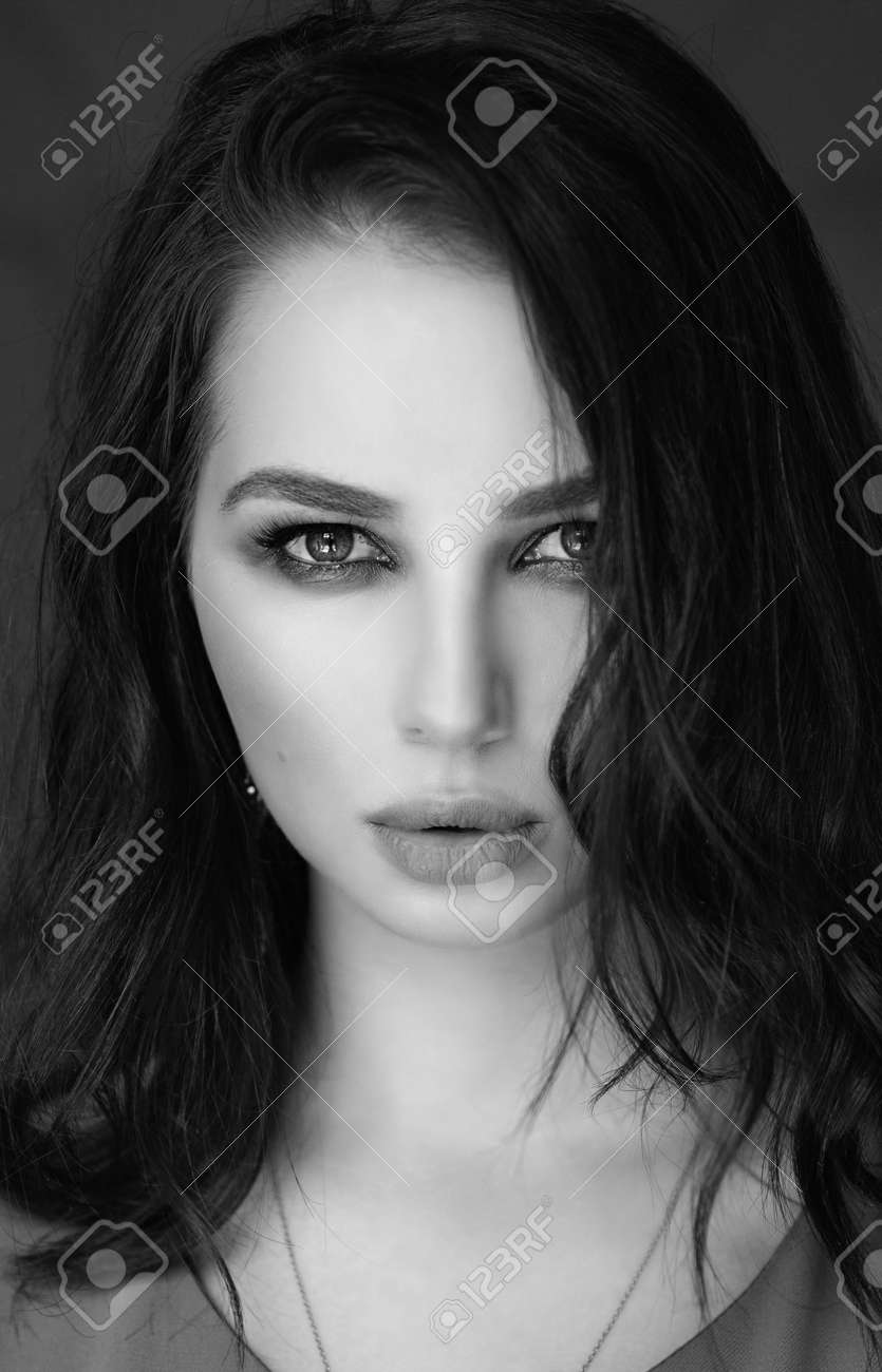 portrait of a woman with dark hair and makeup on her face - 159280821