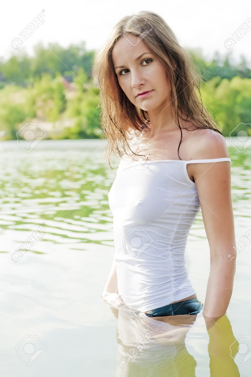 Beautiful Girl In Wet T Shirt Stands Waist Deep In Water Stock Photo