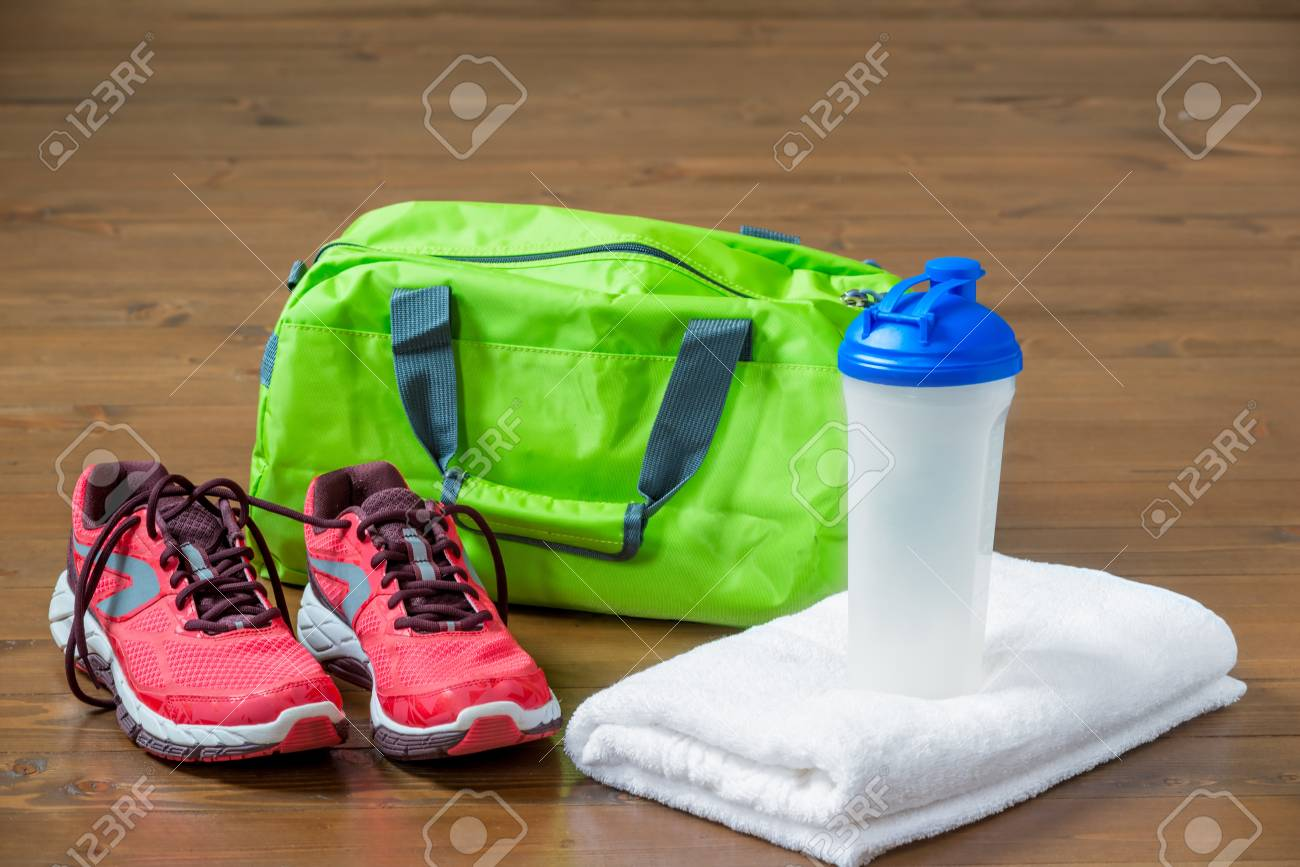 1406325299 Green sports bag and pink sneakers near a towel with a bottle for fitness  Stock Photo
