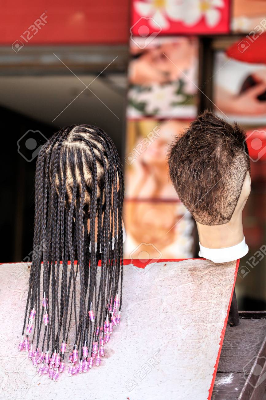 Die Haare auf der Puppe. Beispiele für Frisuren für weiblichen und  männlichen Mannequinkopf. Friseur auf der Straße eines tropischen Landes.  Viele