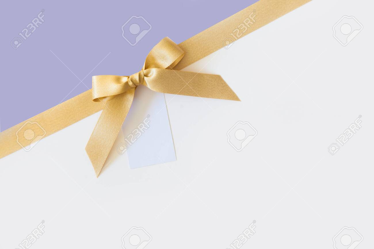Gold ribbon with a bow as a gift on a white and lavender background - 146573946