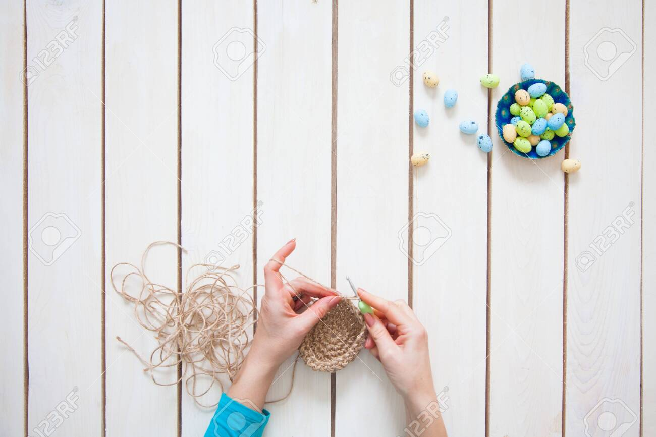 A woman makes a nest for Easter eggs. Easter bunny. White background. A handmade toy. - 147800635