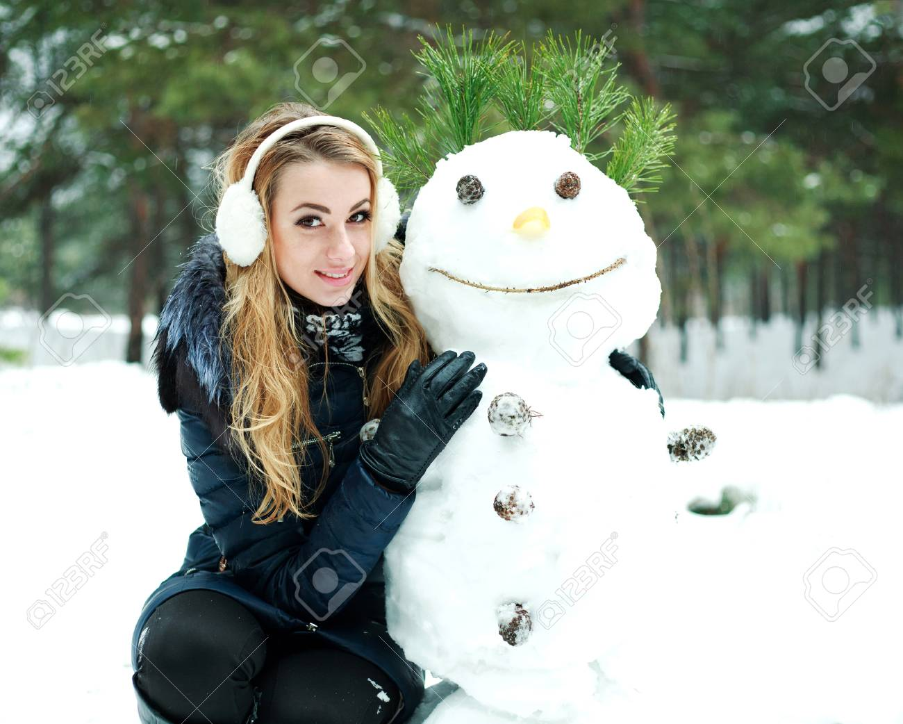 Pretty girl with snowman in pinewood on a winter day Stock Photo - 17415405