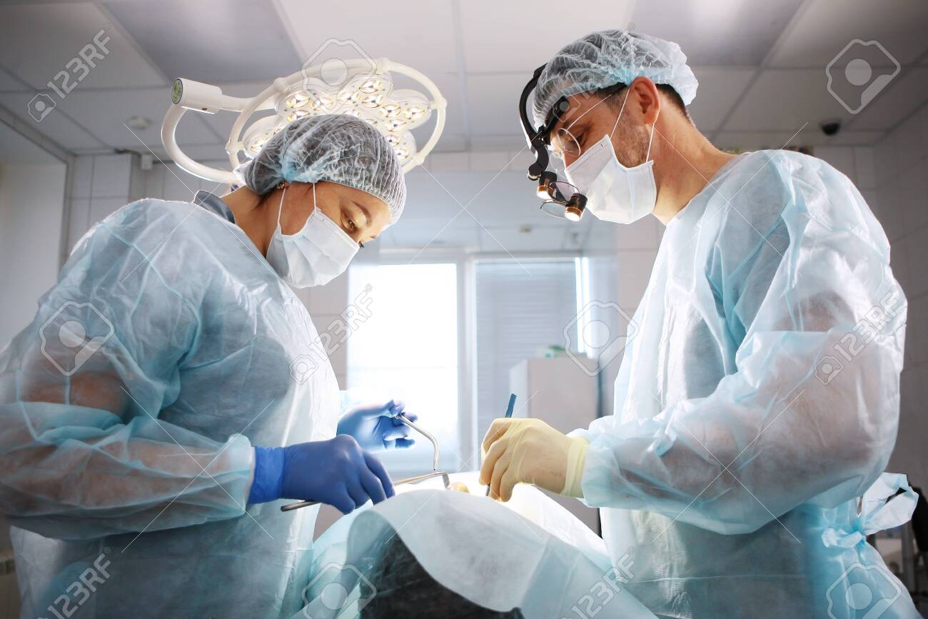 The surgeon, the dentist and the nurse, perform an operation on the patient. The concept of maintaining health and beauty. - 131934810