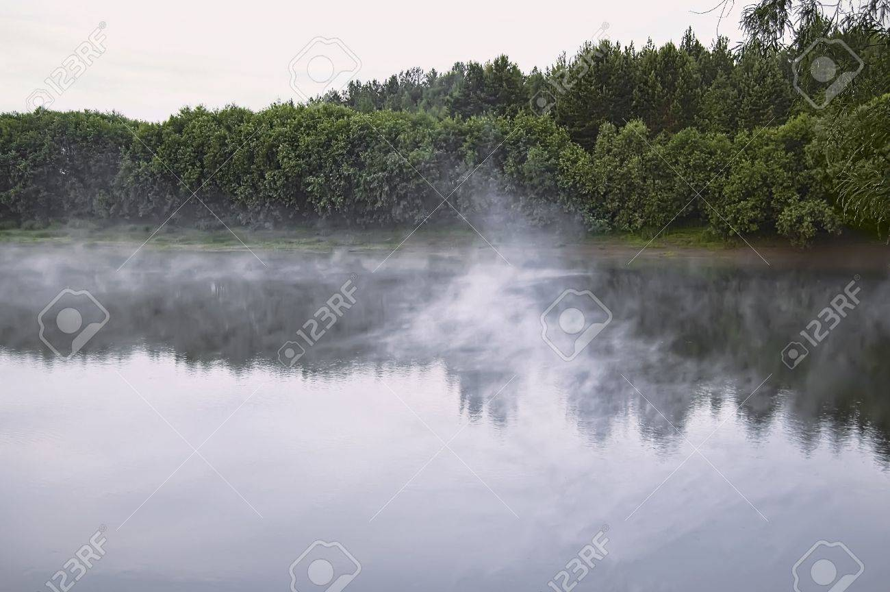Fog over the water of the river, green trees and bushes on the shore, the sky at dawn Stock Photo - 7894484