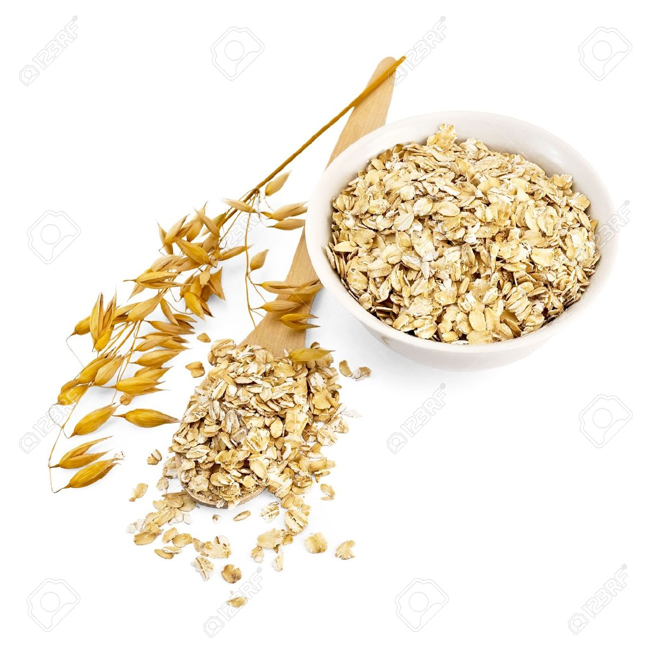 Rolled oats in a wooden spoon and a white porcelain bowl, oat stalks isolated on white background - 12323480