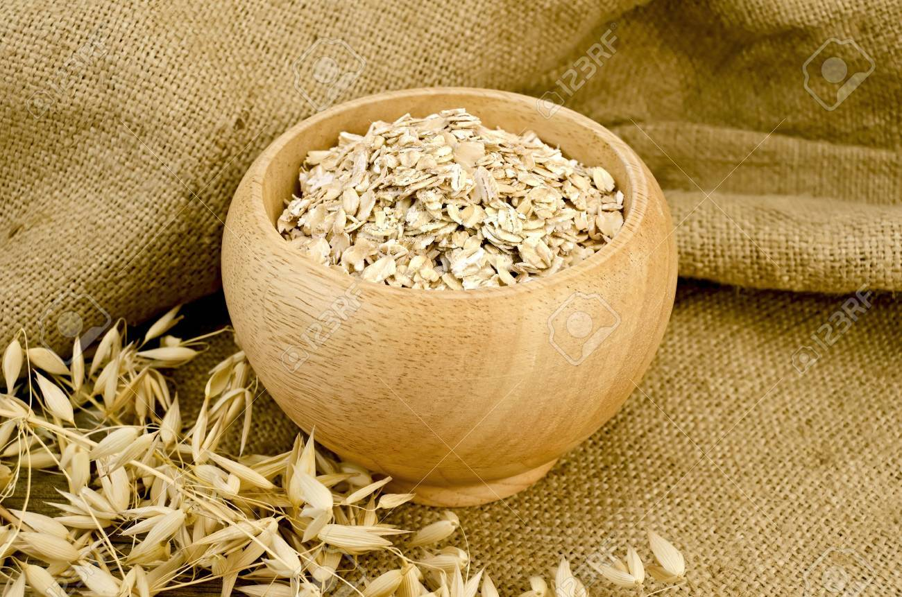 Oat flakes in a wooden bowl, stalks of oats on sackcloth and wooden board Stock Photo - 15321766