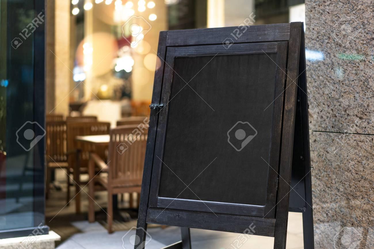 Close up of black sandwich board next to restaurant. - 106925137