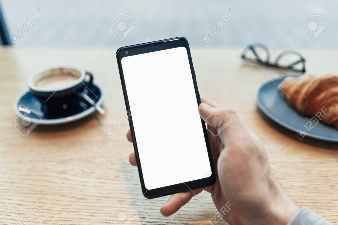 Close up of man tattooed hands holding mobile phone with blank screen. - 114374469