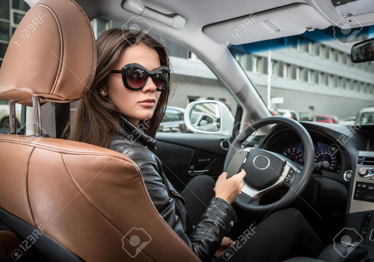 e845d2b472 Girl in sunglasses driving a car Stock Photo - 48290695