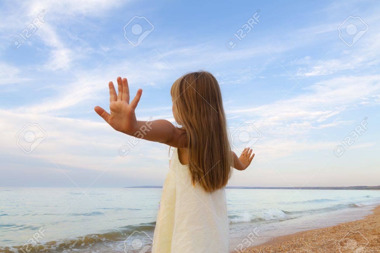 Small cute girl in white dress enjoying sunny day at the beach Stock Photo - 17534836
