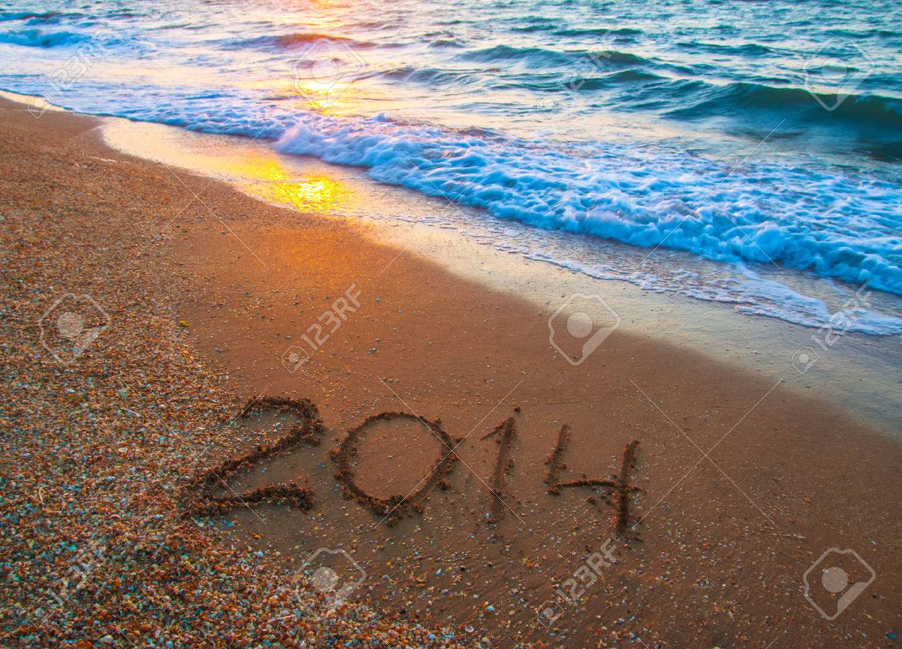 new year 2014 digits on ocean beach sand Stock Photo - 23570326