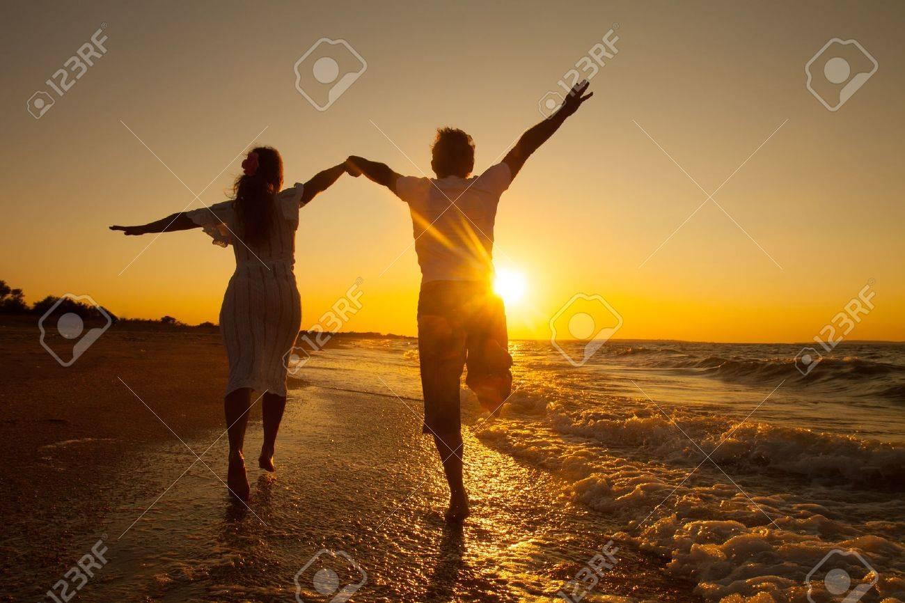 happy couple running on the beach on sunset - 47162163