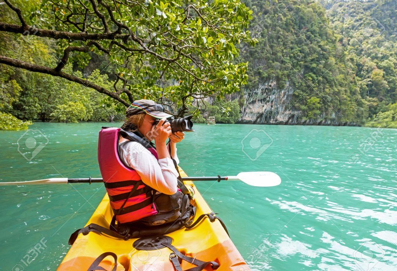 woman on kayak in calm tropical lagoon on koh hong island stock