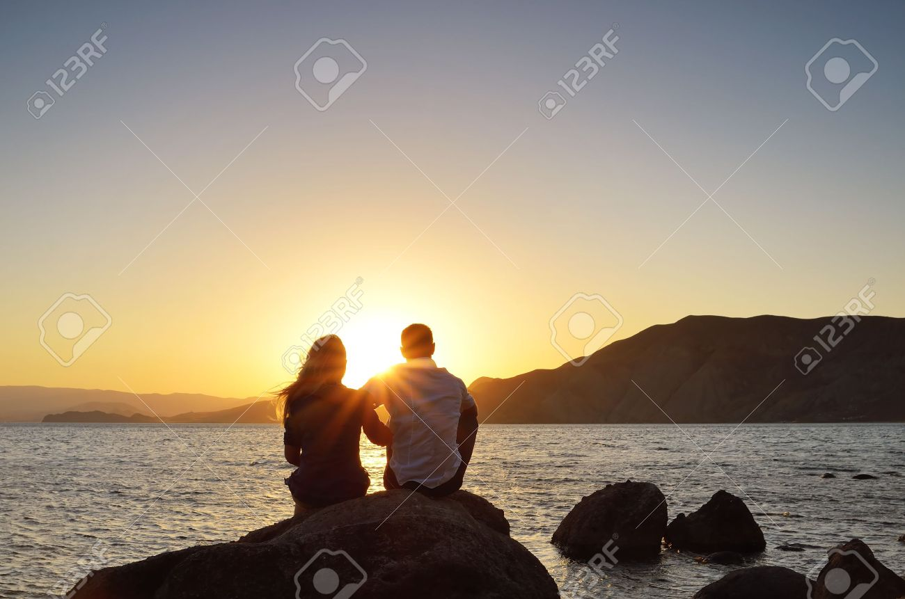 Young couple sitting on a rock near the sea and watching the sun Stock Photo - 14795727