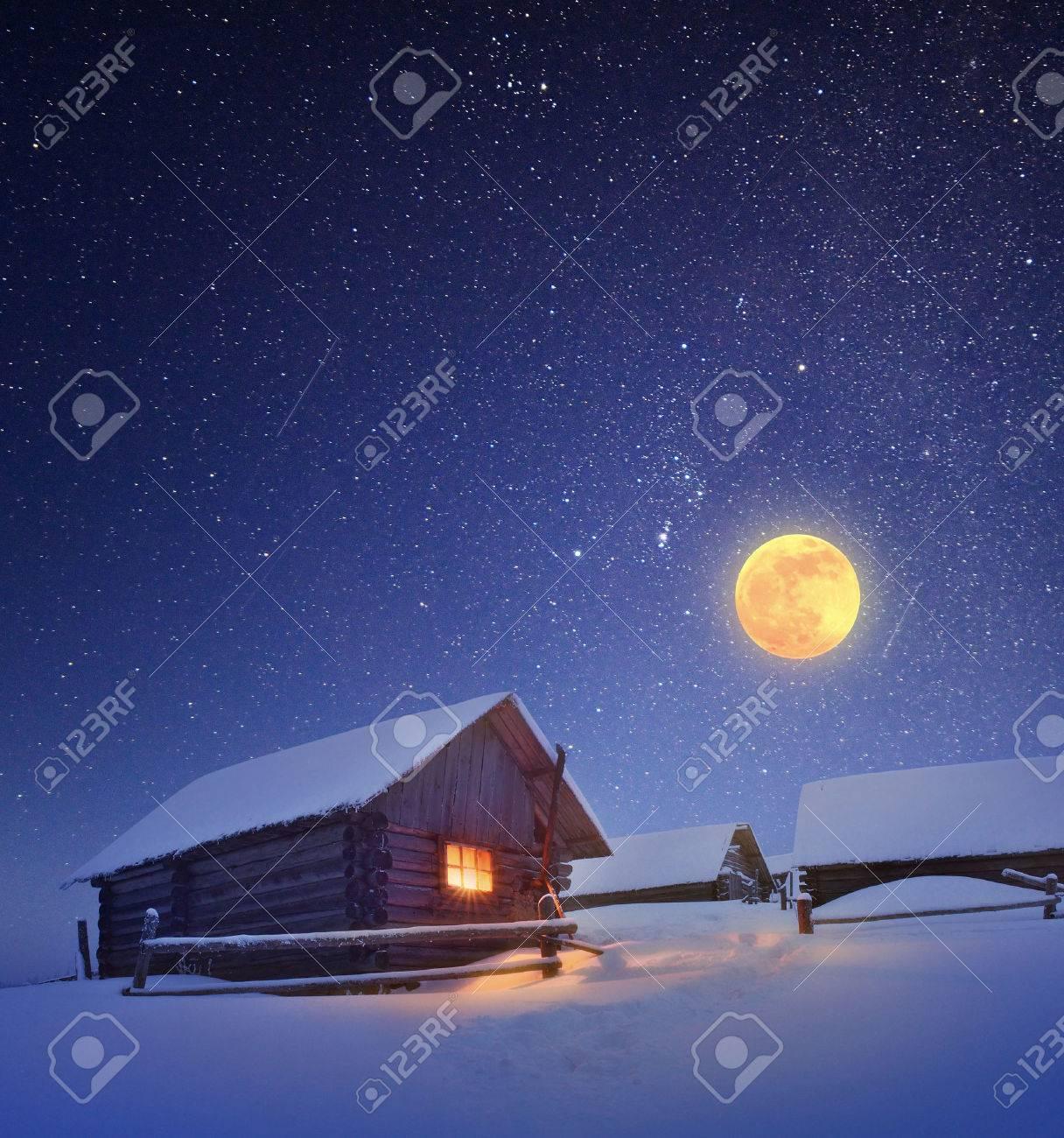 Paysage d'hiver avec un ciel étoilé et la pleine lune La lumière dans la cabine dans les montagnes Banque d'images - 23799306