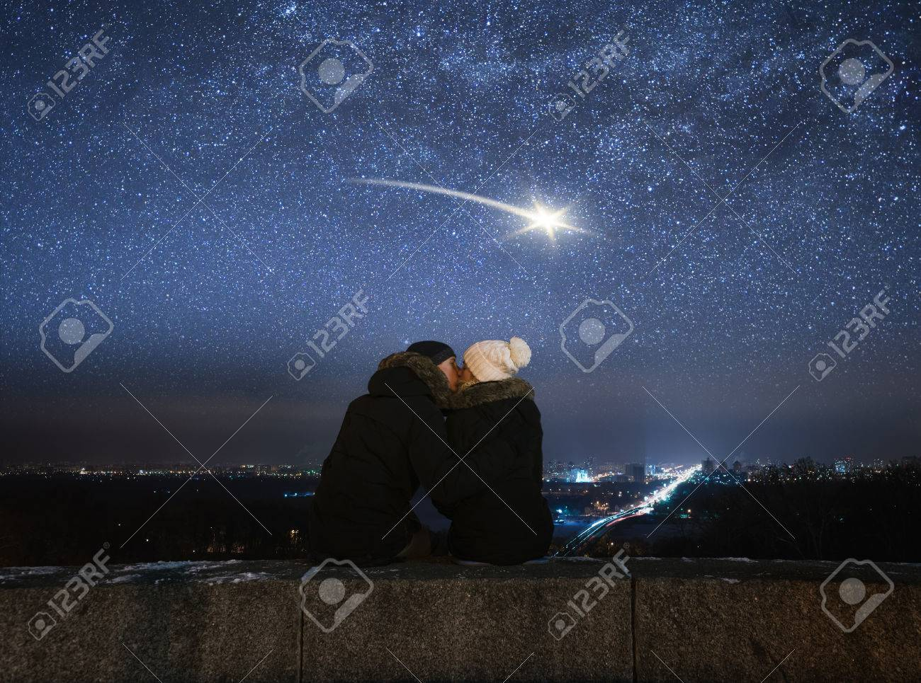Romantic evening. Loving couple kissing. Night in city. Meteor in night sky Banque d'images - 50655429