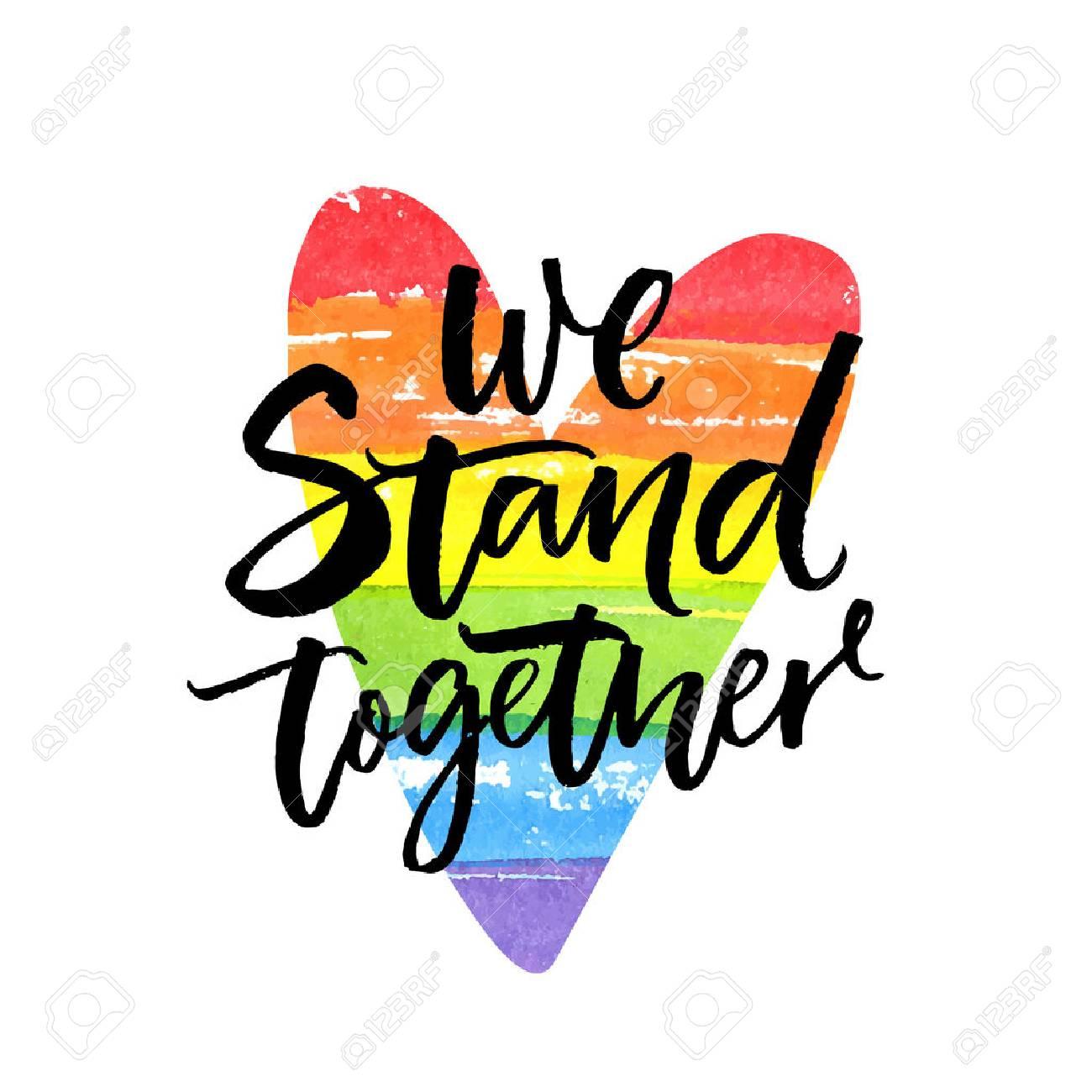 We stand together. Inspirational LGBT slogan han dwritten on rainbow flag heart. - 93880114