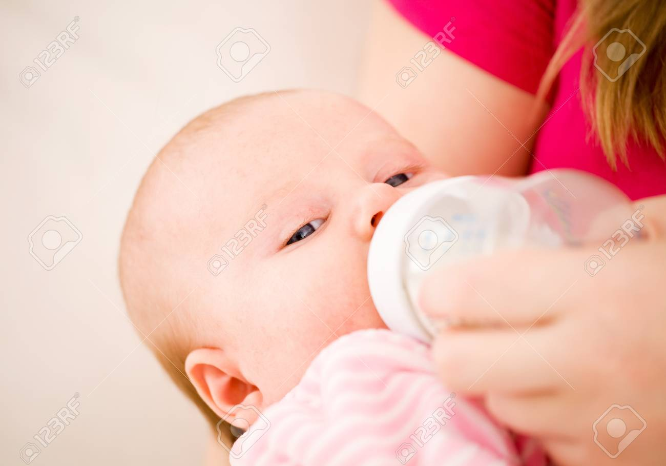 Feeding of the chest baby by a dairy mix from a children's small bottle Stock Photo - 8767533