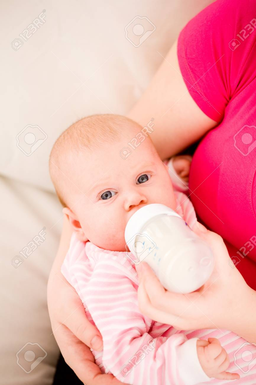 Feeding of the chest baby by a dairy mix from a children's small bottle Stock Photo - 9060315