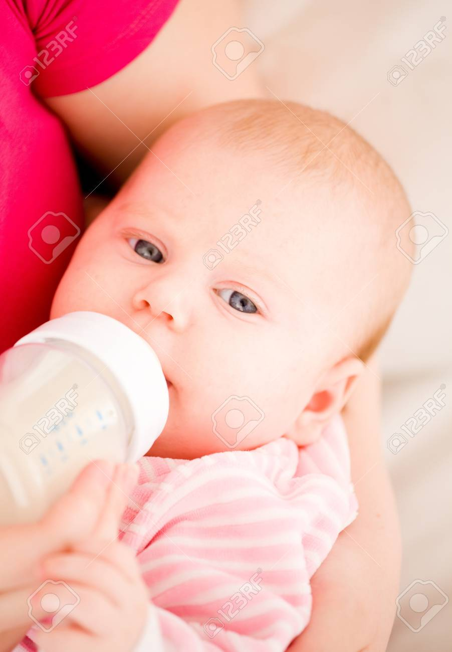 Feeding of the chest baby by a dairy mix from a children's small bottle Stock Photo - 9139151