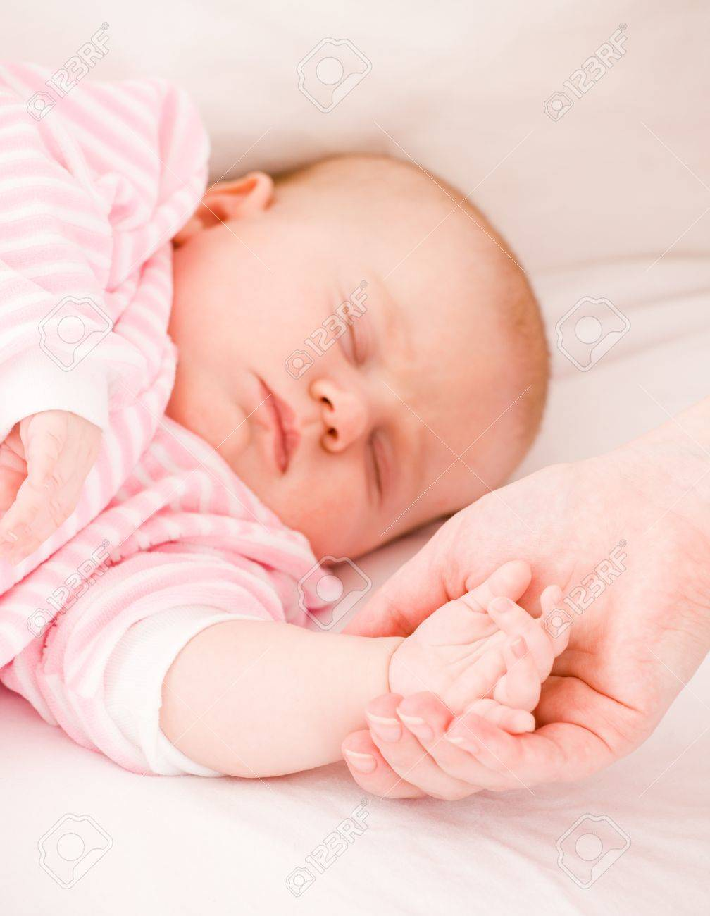 Mum holds by the hand the sleeping baby. Stock Photo - 9958491