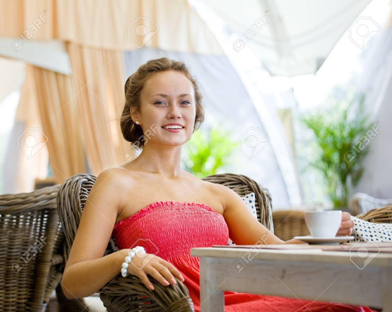 Young girl in a pink dress seated at a table in the summer restaurant Stock Photo - 11956351