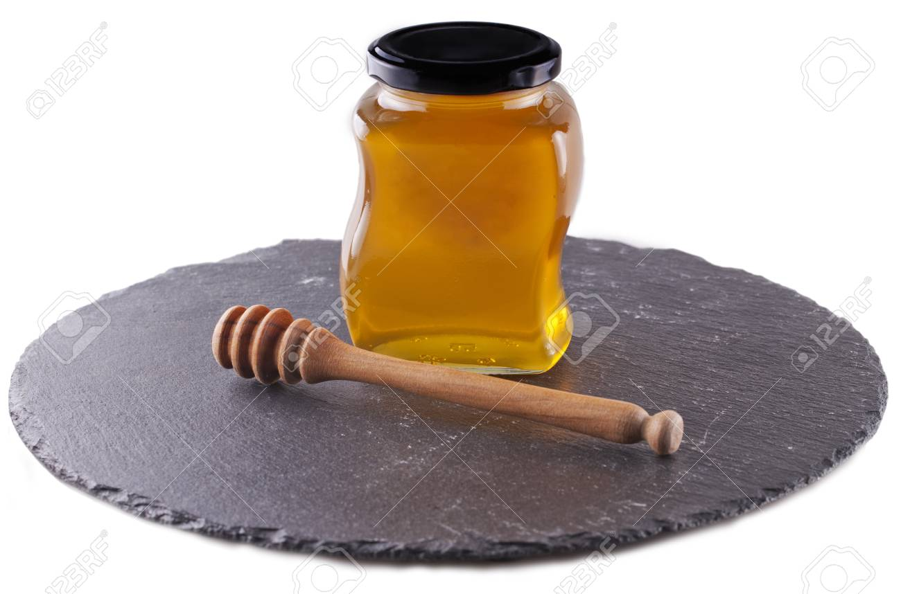 Honey with honey spoon over a black stone plate Stock Photo - 17038432