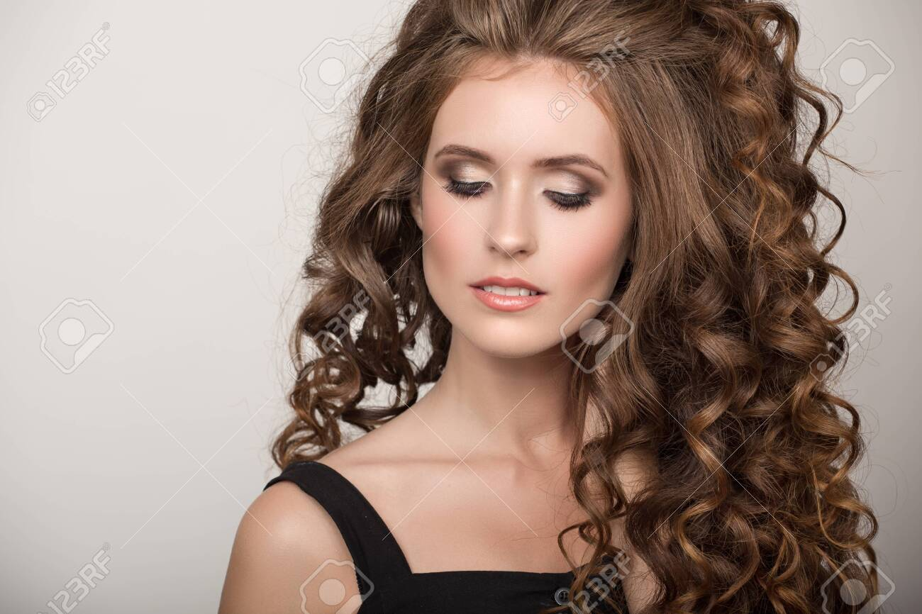 Beautiful woman with curly brown thick hair. Face closeup portrait - 129517253