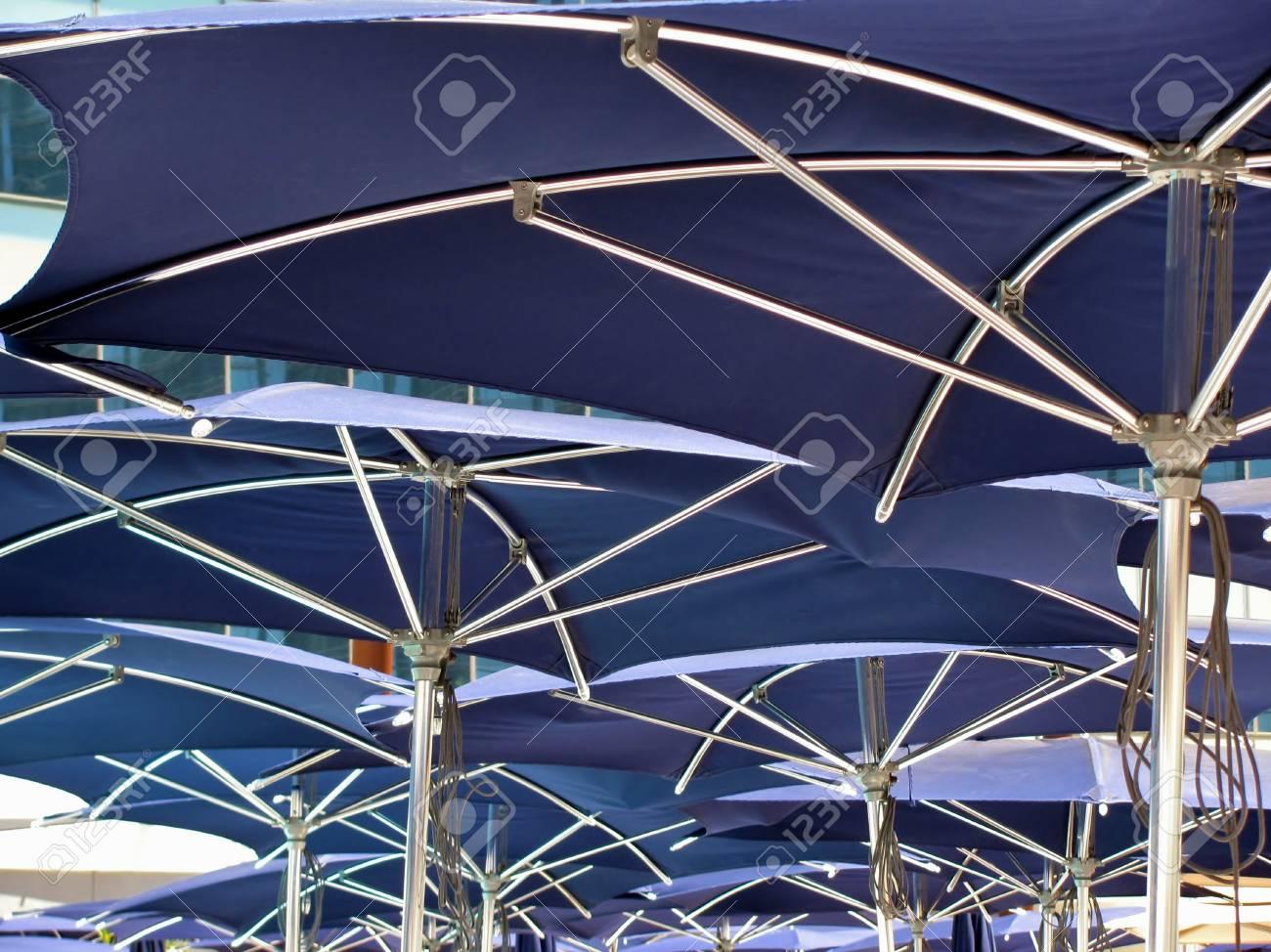 Under the blue swimming pool umbrellas