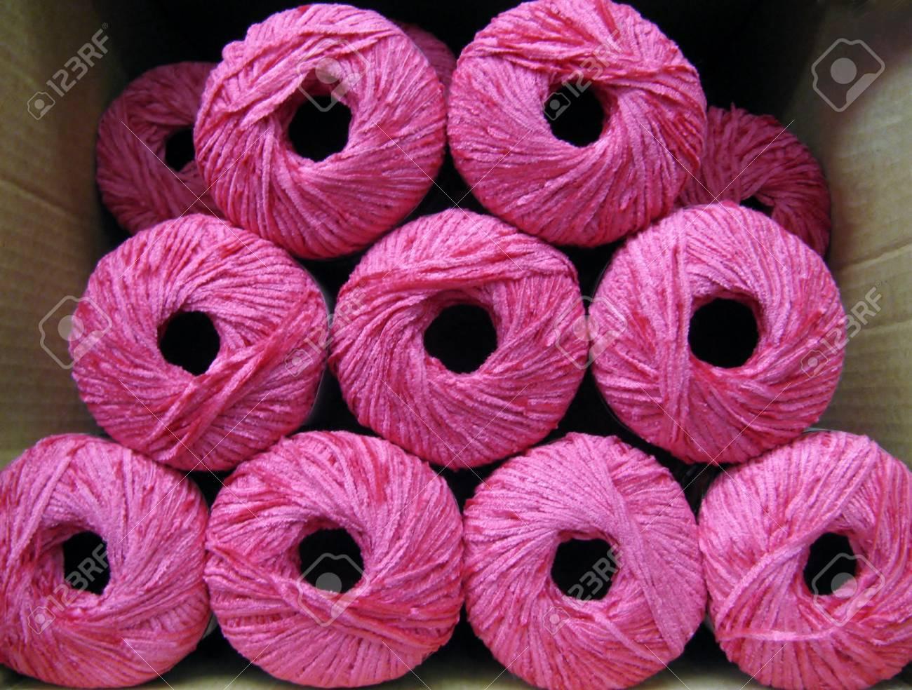 Set of bright pink rayon chenille yarn balls in a carton box