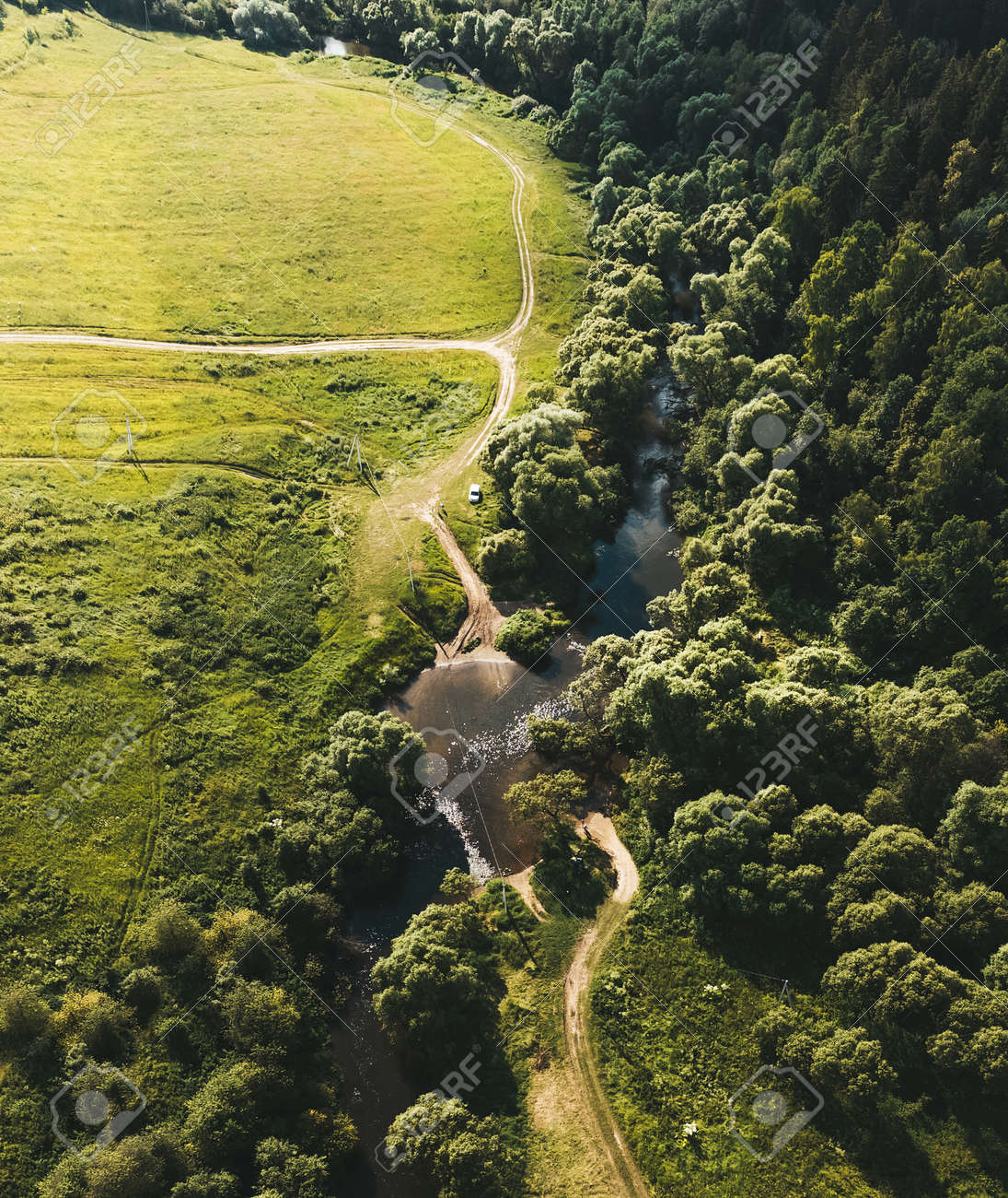 Small river between the field and the forest. Aerial view. Vertical layout. Drone photography - 171661841