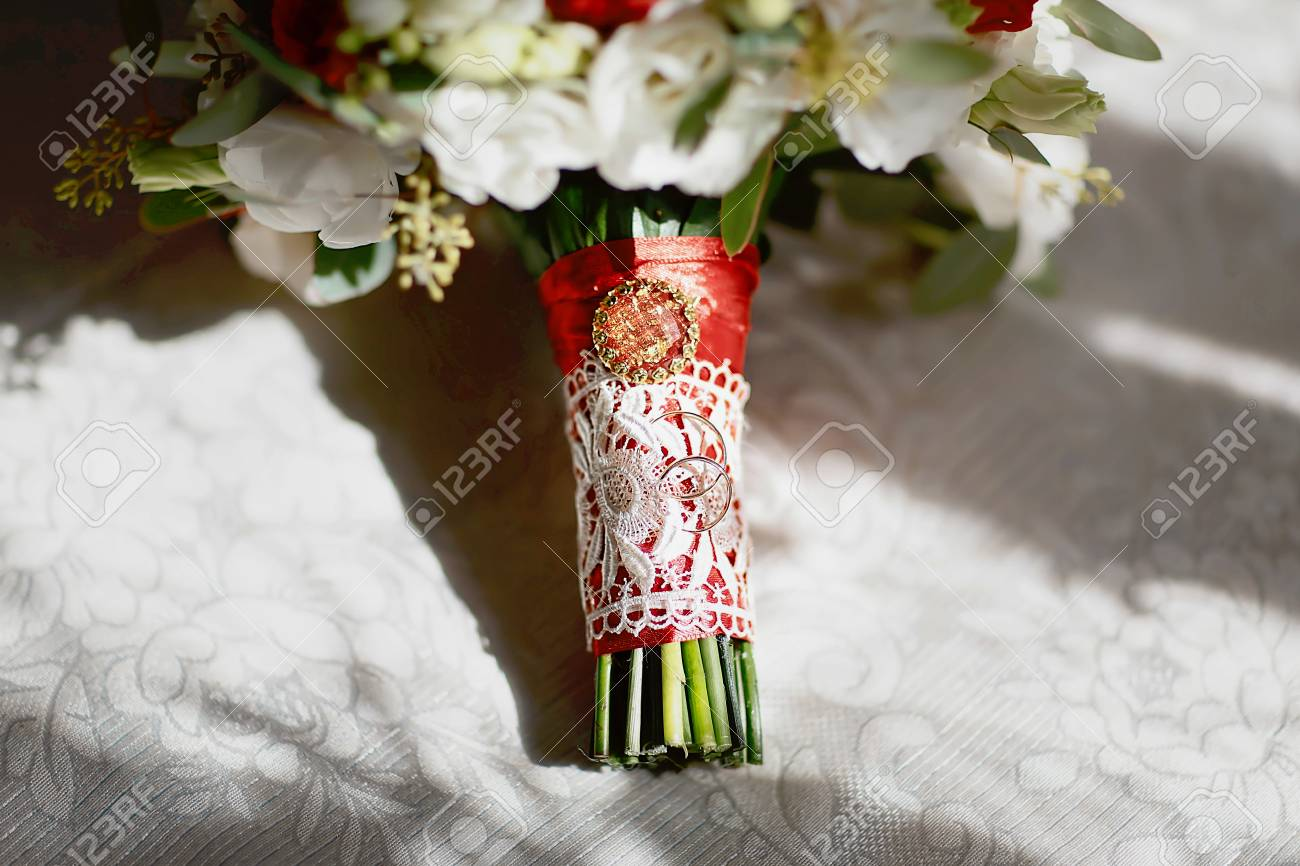 Gold wedding rings on a bouquet of flowers with white lace and gold wedding rings on a bouquet of flowers with white lace and a red ribbon and izmirmasajfo
