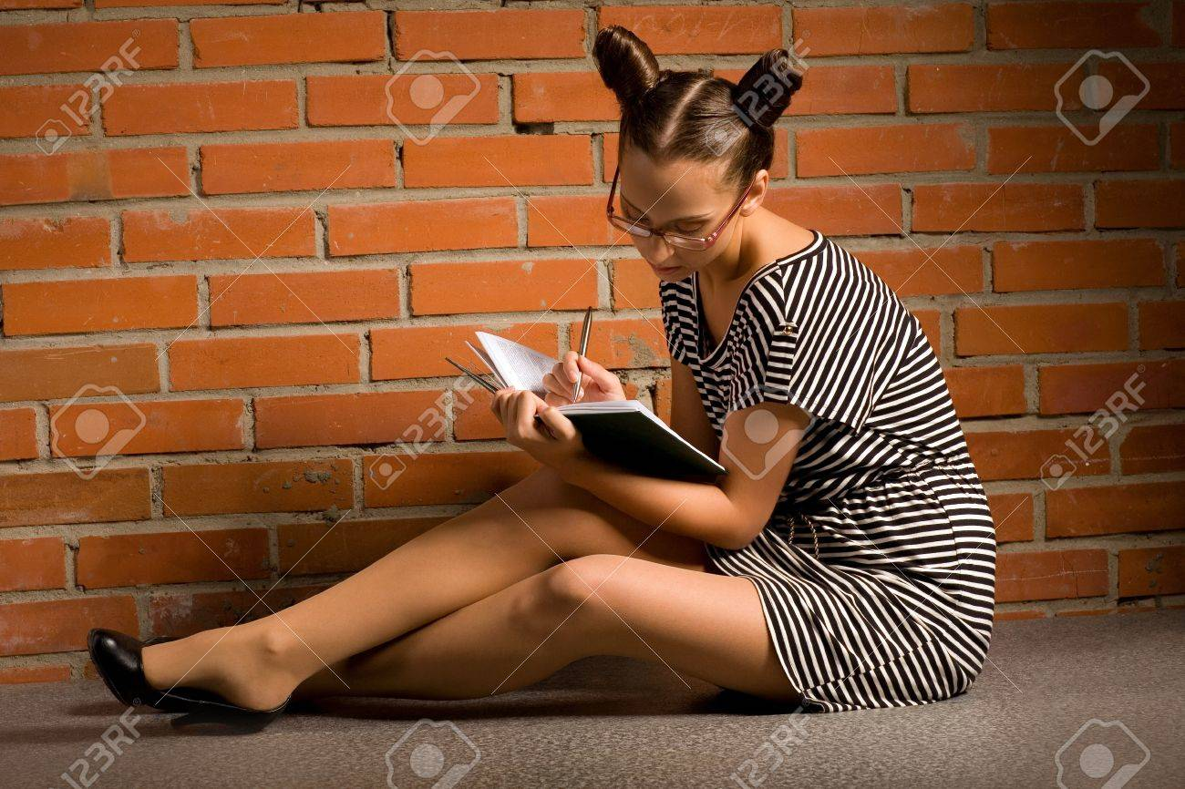 woman with book on brick wall background Stock Photo - 9519088
