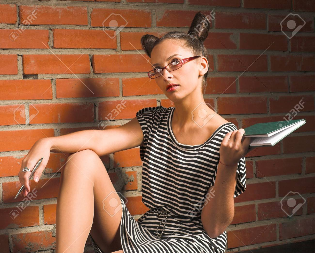 woman with book on brick wall background Stock Photo - 11410700