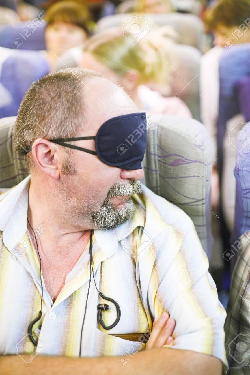 manture man in sleeping mask in the airplane - 11417832