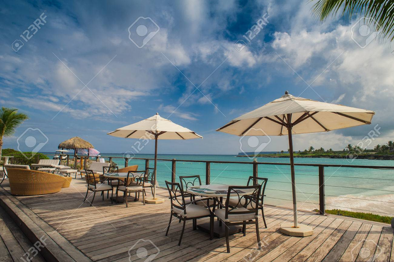 Outdoor restaurant at the beach. Cafe on the beach, ocean and sky. Table setting at tropical beach restaurant. Dominican Republic, Seychelles, Caribbean, Bahamas. Relaxing on remote Paradise beach. - 39002777