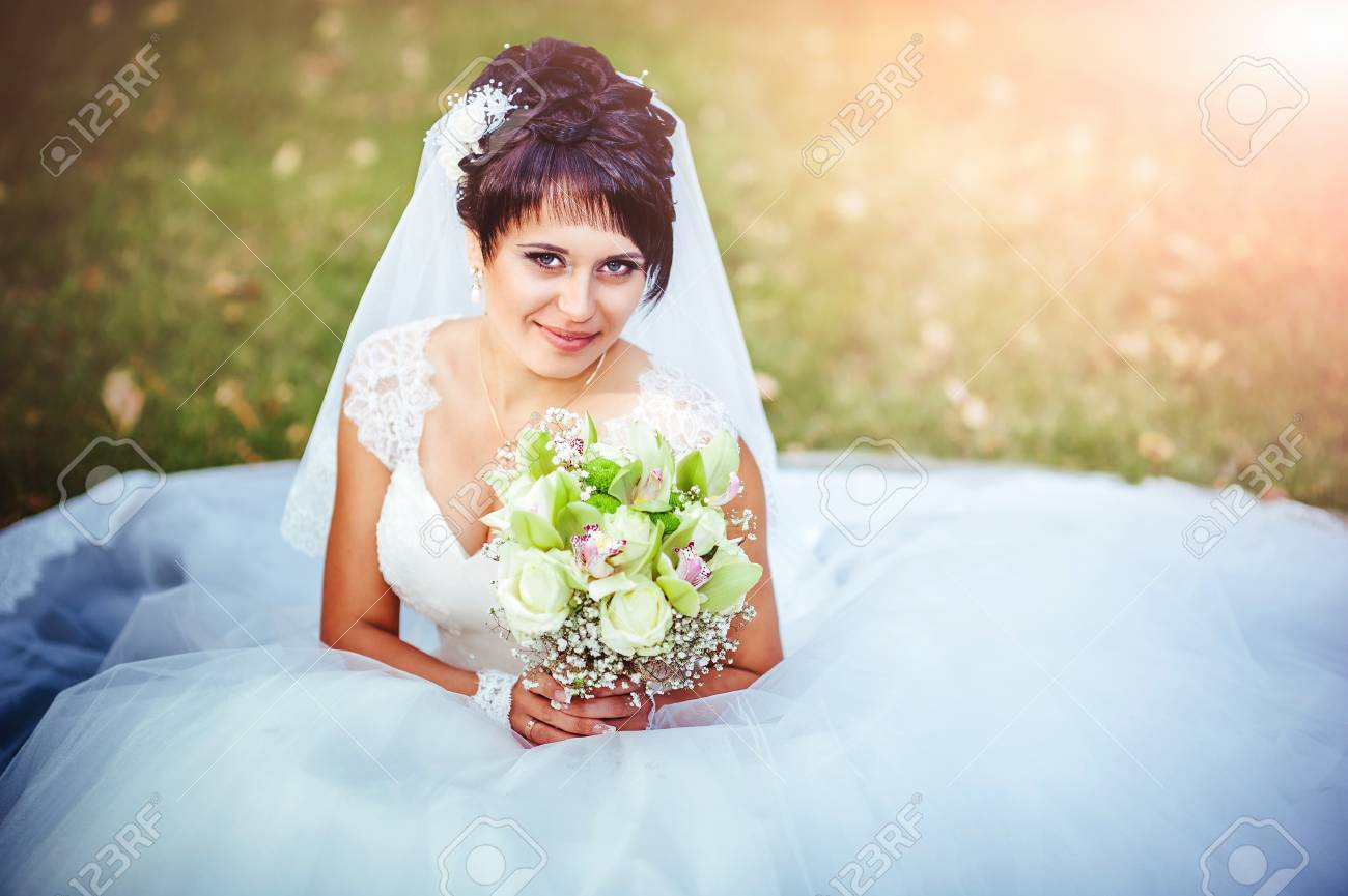 Portrait Of Beautiful Young Bride Holding Bright Bouquet Of Flowers