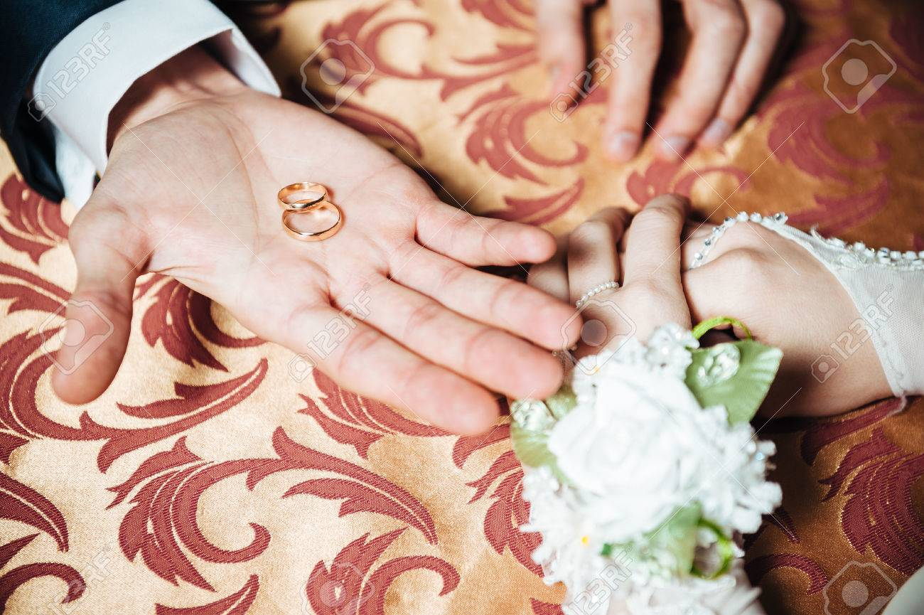 Mehndi Hands Couple : Couple s hands on the table and wedding rings bridal bouquet