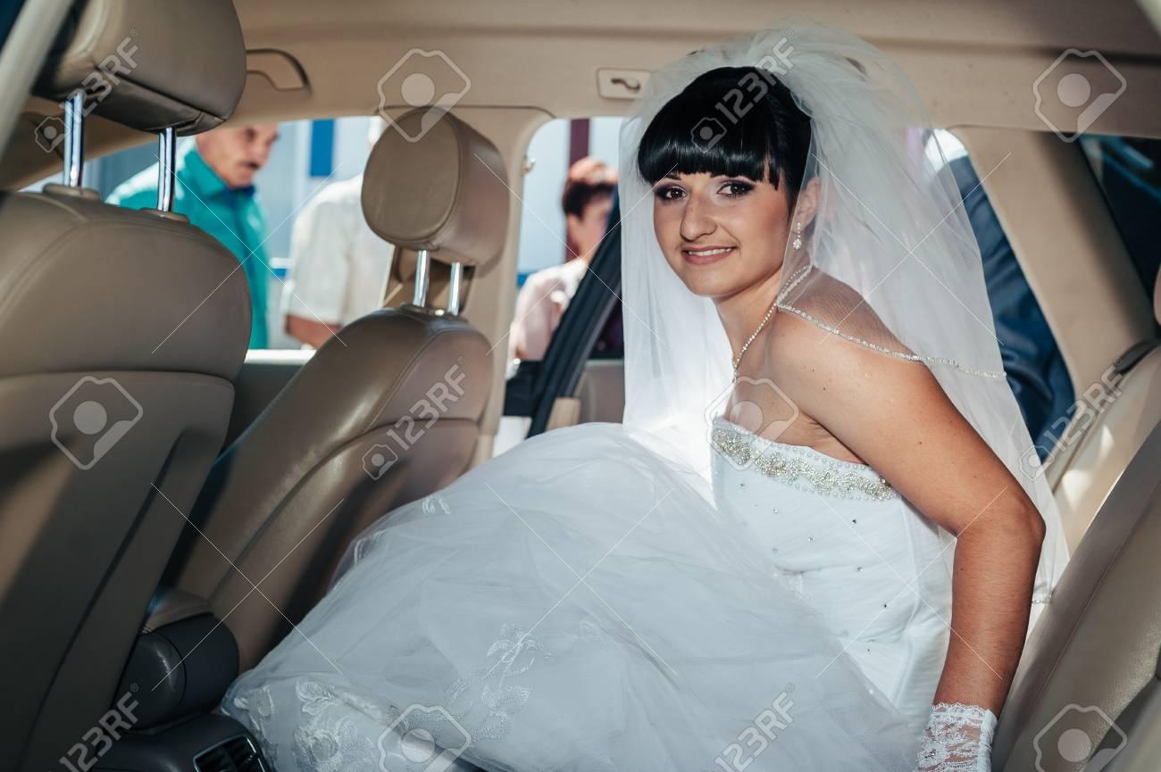 Happy bride sitting in limousine holding flower bouquet. - 39838798