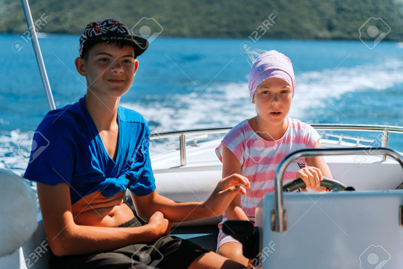 beautiful girl drive the speed boat in Greece. Little girl on a private yacht in the sea. Attractive young girl in posing on a yacht at a sunny summer day. - 168823998