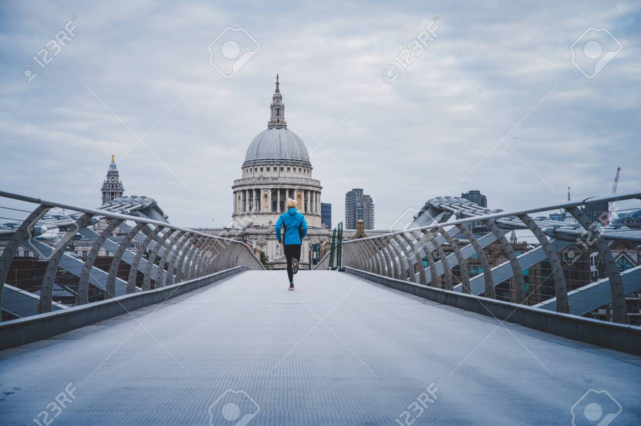 Running in London, Morning run at Millennium Footbridge over the Thames. St Paul's Cathedral in background.. - 135589296