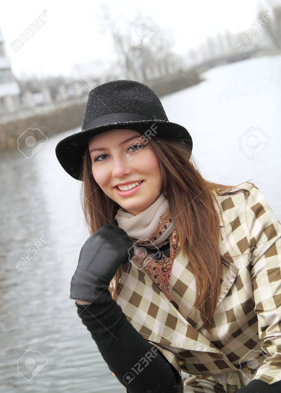 417769b6358 Woman in hat smiling in cold raining weather Stock Photo - 43059773