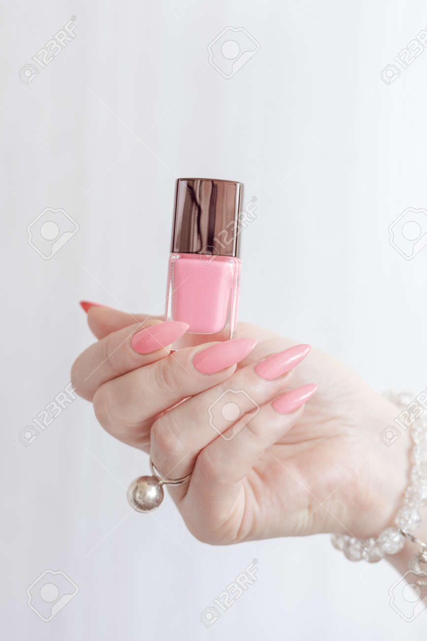 Female hand with long nails and a bottle of pink nail polish - 162761865