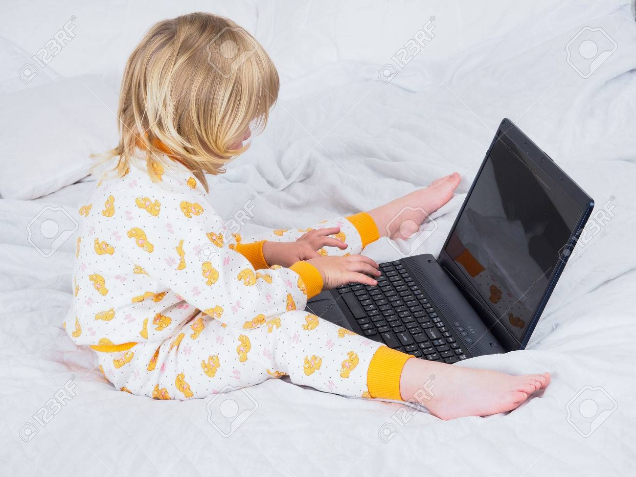 e8b1e6fa11 The baby is sitting in bed in my pajamas and barefoot with a laptop. Visible  heel. A small child is working at the computer. The screen can be supplied  of ...