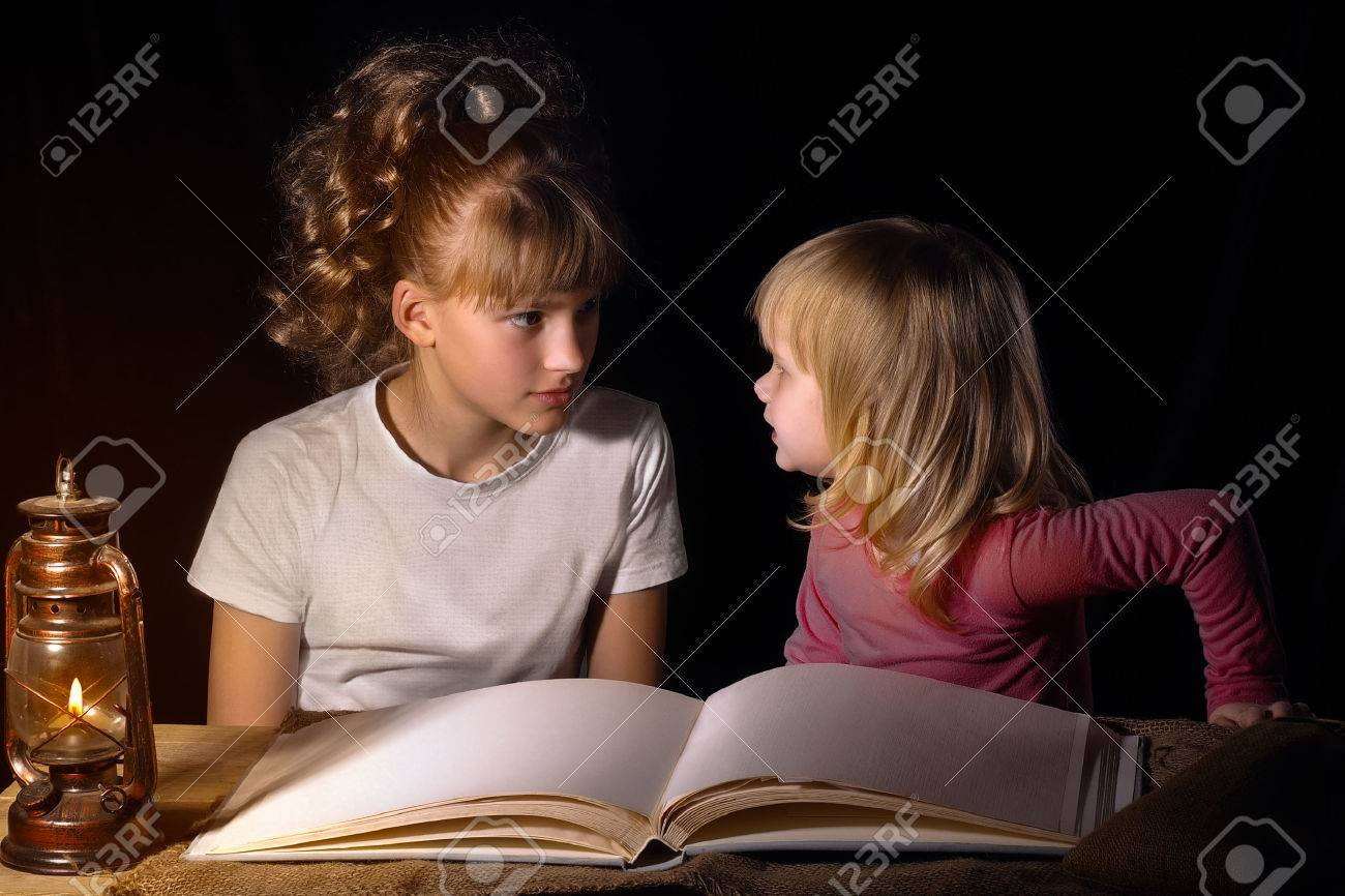 Two sisters tell each other scary stories at night  Open book,